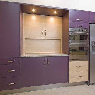 This is an example of a mid-sized modern u-shaped open plan kitchen in Sydney with flat-panel cabinets, purple cabinets, granite benchtops, stainless steel appliances, ceramic floors, no island and beige floor.