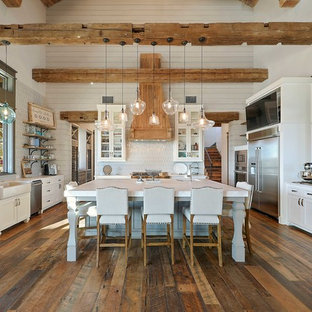 Huge farmhouse eat-in kitchen pictures - Example of a huge cottage u-shaped medium tone wood floor and brown floor eat-in kitchen design in Austin with white cabinets, an island, a farmhouse sink, shaker cabinets, white backsplash, stainless steel appliances and white countertops