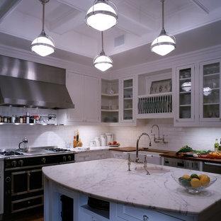 Geschlossene, Große Klassische Küche in L-Form mit Unterbauwaschbecken, Glasfronten, weißen Schränken, Marmor-Arbeitsplatte, Küchenrückwand in Weiß, Rückwand aus Metrofliesen, Küchengeräten aus Edelstahl, braunem Holzboden und Kücheninsel in New York