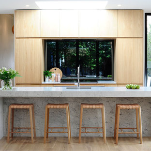 This is an example of a contemporary galley kitchen in Melbourne with an undermount sink, flat-panel cabinets, light wood cabinets, window splashback, stainless steel appliances and an island.