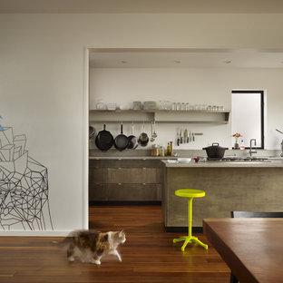 Foto di una piccola cucina minimalista con top in acciaio inossidabile, lavello a vasca singola, ante lisce, ante in legno scuro, paraspruzzi grigio, elettrodomestici in acciaio inossidabile, pavimento in legno massello medio e isola