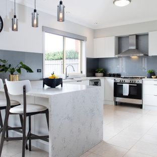 Contemporary u-shaped kitchen in Melbourne with flat-panel cabinets, white cabinets, grey splashback, stainless steel appliances, a peninsula, beige floor and white benchtop.