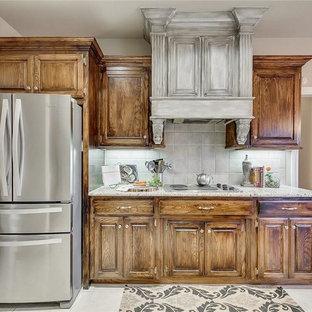Modelo de cocina comedor en U, de estilo americano, pequeña, con armarios con paneles con relieve, puertas de armario con efecto envejecido, encimera de granito, salpicadero beige, salpicadero de travertino y suelo de baldosas de porcelana