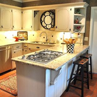 Idee per una piccola cucina tradizionale con lavello a tripla vasca, ante beige, top in granito, paraspruzzi beige, paraspruzzi con piastrelle in pietra, elettrodomestici in acciaio inossidabile, pavimento in mattoni, ante con riquadro incassato e penisola