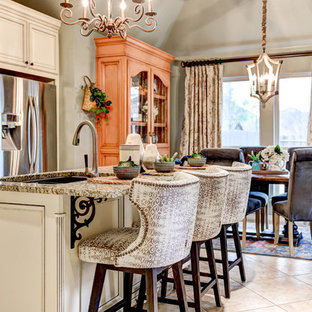Inspiration for a mid-sized traditional single-wall eat-in kitchen in Oklahoma City with an undermount sink, recessed-panel cabinets, white cabinets, granite benchtops, beige splashback, ceramic splashback, stainless steel appliances, ceramic floors, with island, beige floor and beige benchtop.