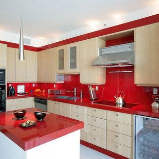 На фото: угловая кухня в современном стиле с двойной раковиной, плоскими фасадами, светлыми деревянными фасадами, красным фартуком и красной столешницей