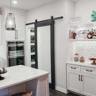 他の地域の小さいインダストリアルスタイルのおしゃれなキッチン (エプロンフロントシンク、シェーカースタイル扉のキャビネット、白いキャビネット、クオーツストーンカウンター、白いキッチンパネル、サブウェイタイルのキッチンパネル、シルバーの調理設備の、濃色無垢フローリング) の写真