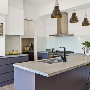 Photo of a contemporary kitchen in Melbourne with a double-bowl sink, flat-panel cabinets, white cabinets, concrete benchtops, white splashback, glass sheet splashback, stainless steel appliances, light hardwood floors, a peninsula and grey benchtop.
