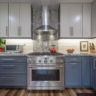 Design ideas for a large country l-shaped kitchen pantry in Miami with a farmhouse sink, shaker cabinets, blue cabinets, granite benchtops, beige splashback, shiplap splashback, stainless steel appliances, vinyl floors, a peninsula, brown floor and multi-coloured benchtop.
