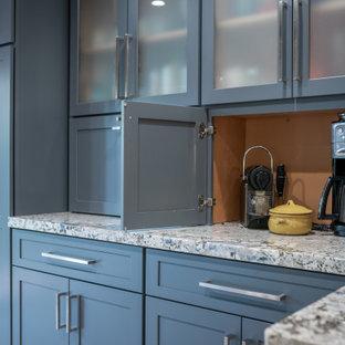 Идея дизайна: большая угловая кухня в стиле кантри с кладовкой, раковиной в стиле кантри, фасадами в стиле шейкер, синими фасадами, гранитной столешницей, бежевым фартуком, фартуком из вагонки, техникой из нержавеющей стали, полом из винила, полуостровом, коричневым полом и разноцветной столешницей