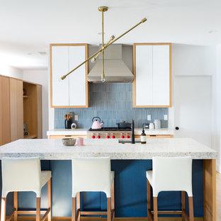 Immagine di una grande cucina contemporanea con lavello sottopiano, ante lisce, ante blu, top in cemento, paraspruzzi blu, paraspruzzi con piastrelle in ceramica, elettrodomestici in acciaio inossidabile, isola, pavimento in legno massello medio, pavimento marrone e top bianco