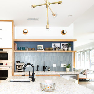 Large midcentury galley open plan kitchen in Los Angeles with an undermount sink, flat-panel cabinets, blue cabinets, concrete benchtops, blue splashback, ceramic splashback, stainless steel appliances, light hardwood floors and with island.