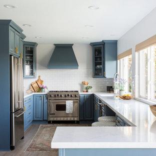 Maritime Küche in U-Form mit Waschbecken, profilierten Schrankfronten, blauen Schränken, Küchenrückwand in Weiß, Rückwand aus Metrofliesen, Küchengeräten aus Edelstahl, Halbinsel und weißer Arbeitsplatte in Los Angeles