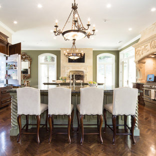 Expansive traditional eat-in kitchen in Los Angeles with raised-panel cabinets, green cabinets, green splashback, stainless steel appliances, multiple islands, a single-bowl sink, granite benchtops, stone slab splashback and dark hardwood floors.
