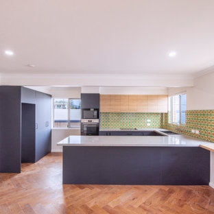 Inspiration for a small midcentury u-shaped kitchen pantry in Central Coast with a drop-in sink, blue cabinets, multi-coloured splashback, black appliances, light hardwood floors, with island and grey benchtop.