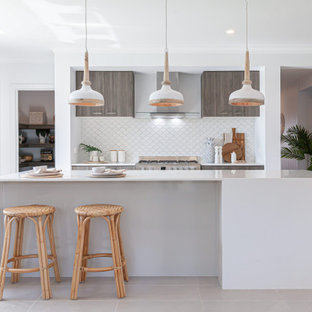 This is an example of a mid-sized tropical galley open plan kitchen in Melbourne with an undermount sink, quartz benchtops, white splashback, ceramic splashback, stainless steel appliances, ceramic floors, with island, beige floor and yellow benchtop.
