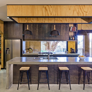 Contemporary kitchen pantry remodeling - Inspiration for a contemporary concrete floor kitchen pantry remodel in Melbourne with concrete countertops, glass sheet backsplash, stainless steel appliances and an island