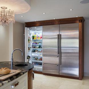 Expansive contemporary open plan kitchen in London with granite worktops, black splashback, glass sheet splashback, stainless steel appliances and an island.