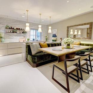 ロンドンの広いコンテンポラリースタイルのおしゃれなキッチン (フラットパネル扉のキャビネット、淡色木目調キャビネット、大理石カウンター、大理石のキッチンパネル、磁器タイルの床、白い床、黒い調理設備) の写真