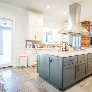 This is an example of a large rural galley kitchen/diner in Austin with a belfast sink, shaker cabinets, white cabinets, granite worktops, grey splashback, glass tiled splashback, stainless steel appliances, cement flooring, multiple islands and grey floors.