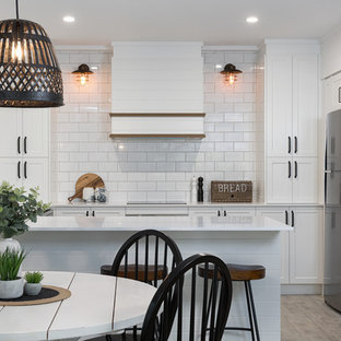 Beach style l-shaped eat-in kitchen in Sunshine Coast with a drop-in sink, shaker cabinets, white cabinets, white splashback, subway tile splashback, stainless steel appliances, a peninsula, grey floor and white benchtop.