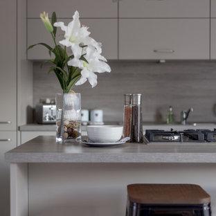 Inredning av ett 60 tals mellanstort grå grått kök, med släta luckor, grå skåp, bänkskiva i kalksten, grått stänkskydd, stänkskydd i marmor, laminatgolv, en köksö och grått golv