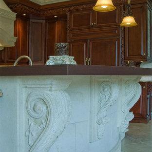 タンパの大きい地中海スタイルのおしゃれなキッチン (アンダーカウンターシンク、レイズドパネル扉のキャビネット、濃色木目調キャビネット、御影石カウンター、ベージュキッチンパネル、石タイルのキッチンパネル、パネルと同色の調理設備、トラバーチンの床、ベージュの床、ベージュのキッチンカウンター) の写真