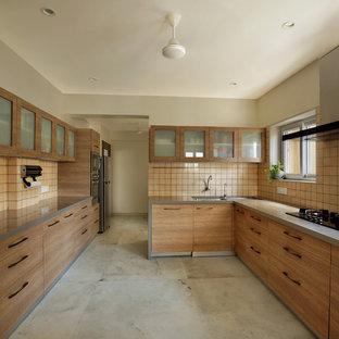 Moderne Küche ohne Insel in U-Form mit Doppelwaschbecken, Glasfronten, hellbraunen Holzschränken, Küchenrückwand in Beige, grauem Boden und grauer Arbeitsplatte in Ahmedabad