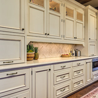 Large traditional eat-in kitchen remodeling - Large elegant l-shaped medium tone wood floor eat-in kitchen photo in Nashville with a farmhouse sink, raised-panel cabinets, beige cabinets, quartz countertops, beige backsplash, stone tile backsplash, stainless steel appliances and an island