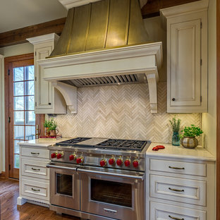 Large traditional eat-in kitchen inspiration - Eat-in kitchen - large traditional l-shaped medium tone wood floor eat-in kitchen idea in Nashville with a farmhouse sink, raised-panel cabinets, beige cabinets, quartz countertops, beige backsplash, stone tile backsplash, stainless steel appliances and an island