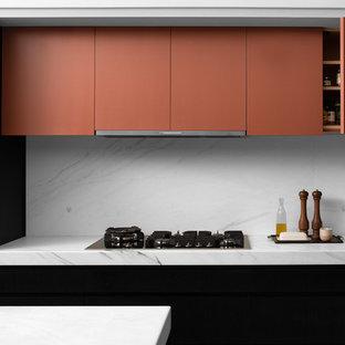 Ejemplo de cocina minimalista, abierta, con fregadero bajoencimera, armarios con paneles lisos, puertas de armario negras, encimera de mármol, salpicadero de mármol, electrodomésticos con paneles, suelo de terrazo, dos o más islas, suelo gris y encimeras blancas