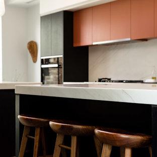 Imagen de cocina minimalista con fregadero bajoencimera, armarios con paneles lisos, puertas de armario negras, encimera de mármol, salpicadero de mármol, electrodomésticos con paneles, suelo de terrazo, dos o más islas, suelo gris y encimeras blancas