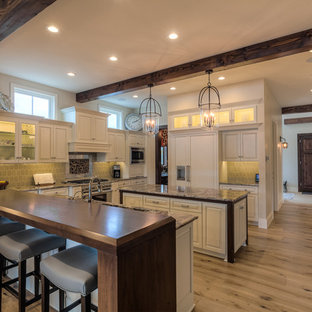 Large country u-shaped separate kitchen in Seattle with multiple islands, an undermount sink, raised-panel cabinets, white cabinets, granite benchtops, grey splashback, stainless steel appliances and light hardwood floors.
