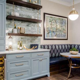 Diseño de cocina comedor clásica renovada con armarios con rebordes decorativos, puertas de armario azules, salpicadero azul, suelo de madera oscura, fregadero bajoencimera, encimera de cuarzo compacto y una isla