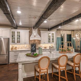 オーランドの中サイズのシャビーシック調のおしゃれなキッチン (エプロンフロントシンク、レイズドパネル扉のキャビネット、白いキャビネット、御影石カウンター、マルチカラーのキッチンパネル、モザイクタイルのキッチンパネル、シルバーの調理設備の、無垢フローリング、茶色い床、マルチカラーのキッチンカウンター) の写真