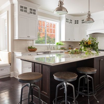 Mid-sized country l-shaped dark wood floor and brown floor eat-in kitchen photo in Seattle with a farmhouse sink, shaker cabinets, white cabinets, white backsplash, subway tile backsplash, an island and stainless steel appliances