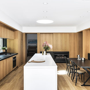 This is an example of a contemporary galley eat-in kitchen in Sydney with a double-bowl sink, flat-panel cabinets, medium wood cabinets, black splashback, window splashback, panelled appliances, medium hardwood floors, with island, brown floor and black benchtop.