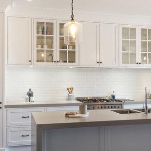 シドニーのビーチスタイルのおしゃれなキッチン (ダブルシンク、フラットパネル扉のキャビネット、白いキャビネット、白いキッチンパネル、サブウェイタイルのキッチンパネル、シルバーの調理設備、濃色無垢フローリング、黒い床) の写真