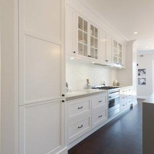 シドニーの小さいビーチスタイルのおしゃれなキッチン (ダブルシンク、フラットパネル扉のキャビネット、白いキャビネット、白いキッチンパネル、サブウェイタイルのキッチンパネル、シルバーの調理設備、濃色無垢フローリング、黒い床) の写真