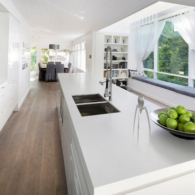 Inspiration for a mid-sized contemporary galley light wood floor and brown floor open concept kitchen remodel in Sydney with flat-panel cabinets, stainless steel appliances, an undermount sink, white cabinets, quartz countertops, white backsplash, glass sheet backsplash and white countertops