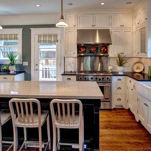 Bild på ett amerikanskt kök, med en rustik diskho, granitbänkskiva, skåp i shakerstil, vita skåp, vitt stänkskydd och rostfria vitvaror