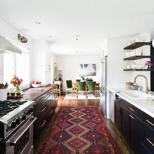 Foto de cocina comedor de galera, clásica renovada, con fregadero encastrado, armarios con paneles lisos, puertas de armario negras, salpicadero blanco, electrodomésticos de acero inoxidable, suelo de madera en tonos medios y península