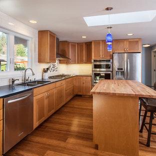 Idéer för stora retro kök, med en undermonterad diskho, skåp i shakerstil, skåp i mellenmörkt trä, bänkskiva i kvarts, vitt stänkskydd, stänkskydd i keramik, rostfria vitvaror, bambugolv och en köksö