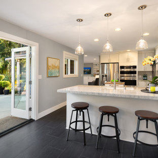 Inspiration for a mid-sized midcentury eat-in kitchen in Seattle with white cabinets, quartzite benchtops, stainless steel appliances, ceramic floors, a peninsula and multi-coloured benchtop.