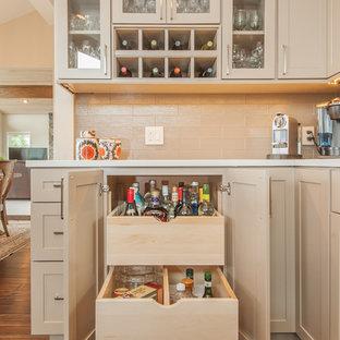 Offene Klassische Küche in L-Form mit Glasfronten, beigen Schränken, Küchenrückwand in Beige, Rückwand aus Metrofliesen, Unterbauwaschbecken, Quarzit-Arbeitsplatte, Küchengeräten aus Edelstahl, braunem Holzboden, Kücheninsel und braunem Boden in Seattle