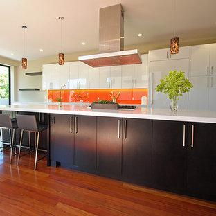 Inspiration for a large contemporary kitchen in Seattle with flat-panel cabinets, medium hardwood floors, white cabinets, quartz benchtops, orange splashback, glass sheet splashback, panelled appliances and with island.