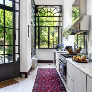Immagine di una cucina lineare minimal con ante lisce, ante grigie, elettrodomestici in acciaio inossidabile, top bianco, paraspruzzi bianco e pavimento bianco