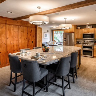 Inspiration for a mid-sized arts and crafts l-shaped eat-in kitchen in Cleveland with a triple-bowl sink, raised-panel cabinets, light wood cabinets, quartz benchtops, grey splashback, subway tile splashback, stainless steel appliances, porcelain floors, with island and grey floor.
