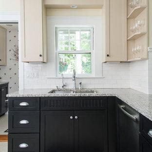 Amerikansk inredning av ett avskilt, mellanstort u-kök, med en dubbel diskho, luckor med infälld panel, beige skåp, granitbänkskiva, vitt stänkskydd, stänkskydd i tunnelbanekakel, rostfria vitvaror, linoleumgolv och en halv köksö