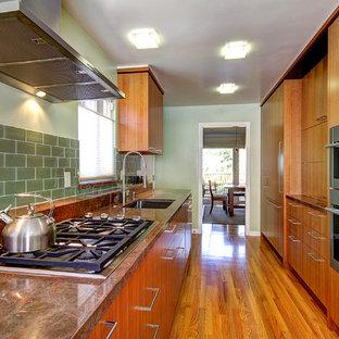 Idéer för avskilda, små funkis parallellkök, med en enkel diskho, släta luckor, skåp i mellenmörkt trä, grönt stänkskydd, stänkskydd i keramik, rostfria vitvaror, mellanmörkt trägolv, bänkskiva i koppar och orange golv